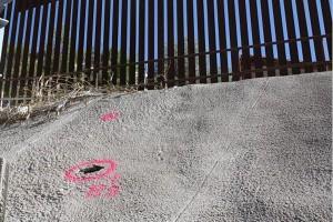 Tunnel beneath a border fence.