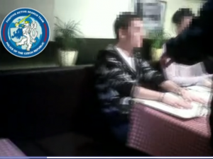 Screenshot of Czech video of suspected hacker under arrest.